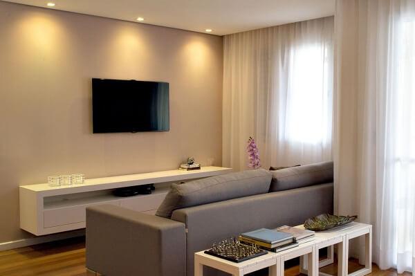 Sala com rack em marcenaria branca e sofá retrátil cinza