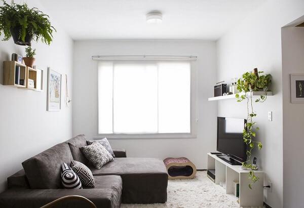 Sala com sofá de veludo marrom e tapete de pelinho branco