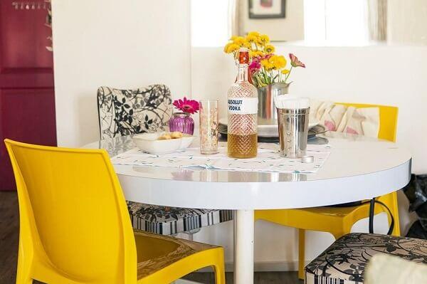 Sala de Jantar com mesa redonda e cadeiras amarela