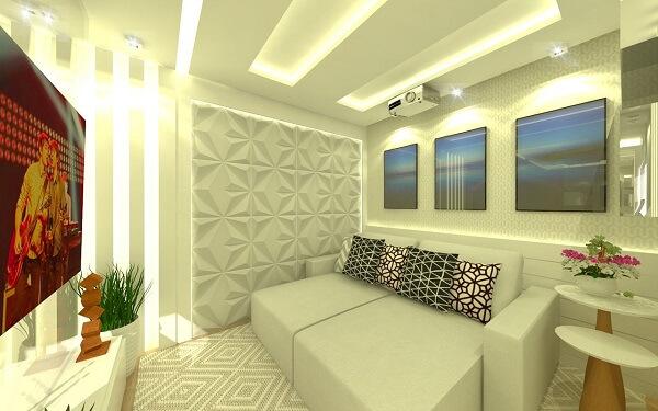 Sala de Tv com revestimento 3D branco, sofá retrátil e almofadas geométricas