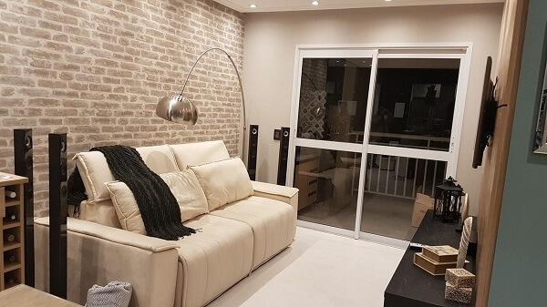 Sala de estar com parede de tijolinho aparente e sofá retrátil claro
