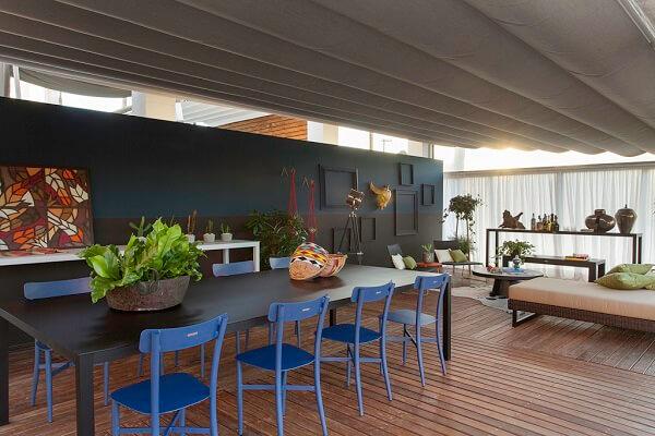 Sala de estar e jantar integradas com parede preta e azul