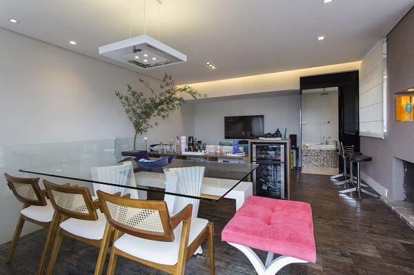 Sala de jantar com cadeira de palinha e mesa de vidro e banco rosa