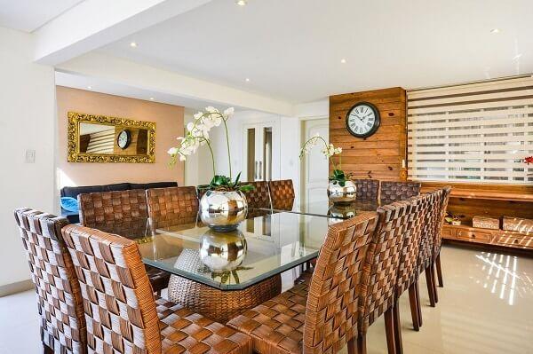Sala de jantar com mesa de vidro e apoio de vime