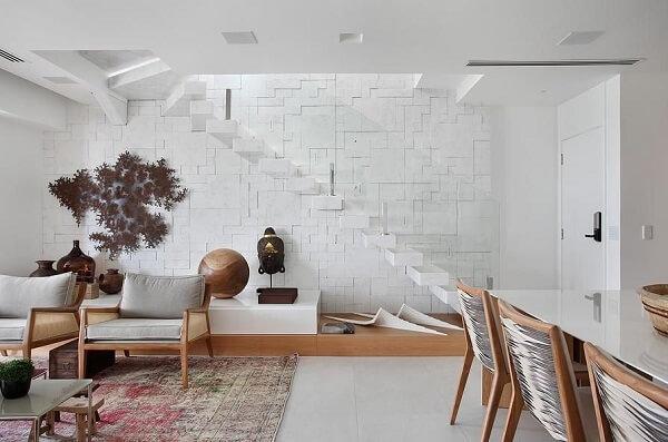 Sala de estar aconchegante com escada branca e guarda corpo de vidro