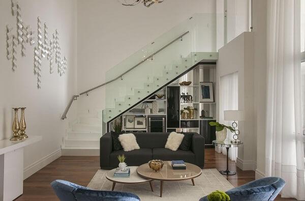 Sofá preto com poltronas de veludo azul e escada com guarda corpo de vidro