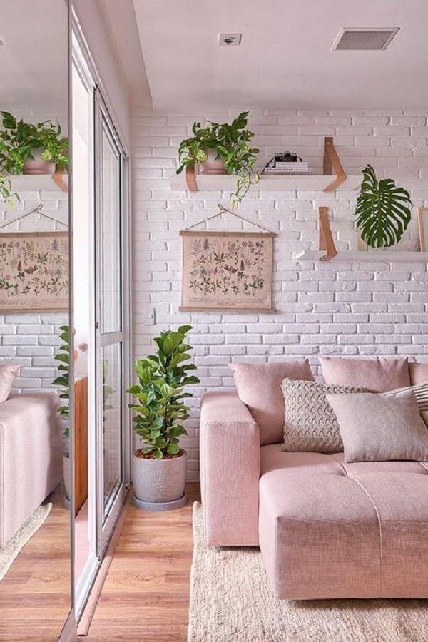 Sofá retrátil de tecido rosa e vaso cerâmico cinza