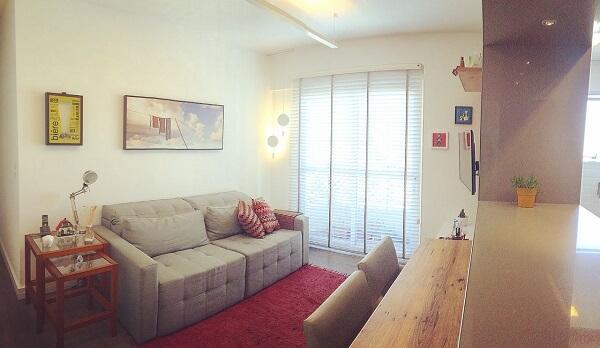 Tapete com tecido vermelho e sofá retrátil bege