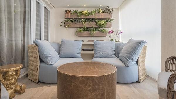 Varanda com sofá em tons neutros, mesa de canto dourada e floreira de madeira
