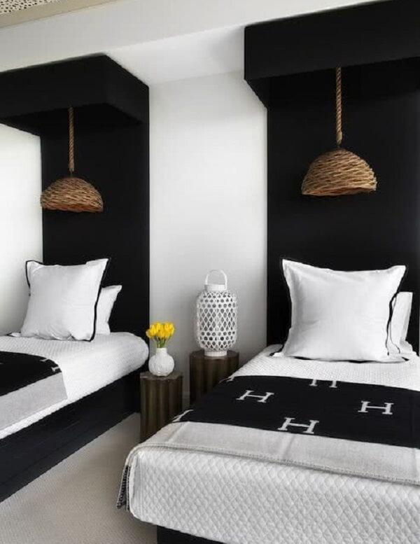 A parede preta delimita a cabeceira das camas do quarto