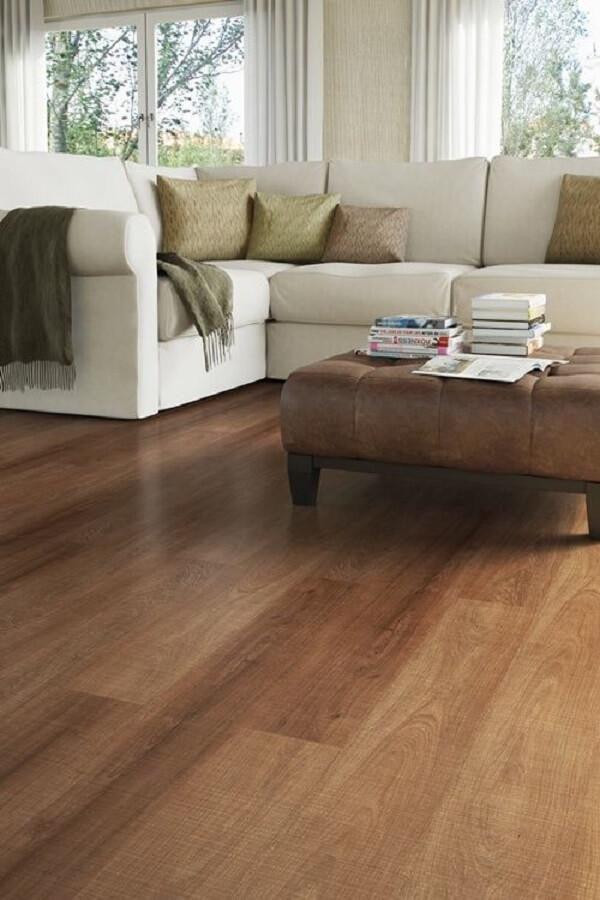 Sala de estar com sofá branco em formato L e piso laminado