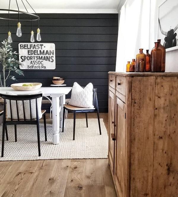 Sala de jantar com parede preta e piso de madeira