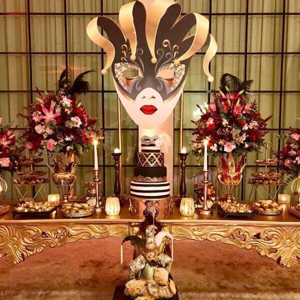 Baile de máscaras com decoração dourada e flores vermelhas