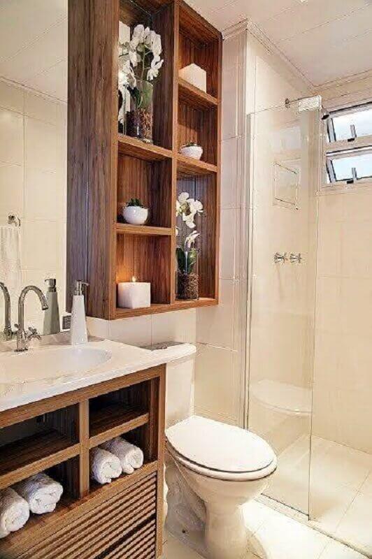 banheiro de apartamento decorado em tons neutros com gabinete e nichos de madeira Foto Só Decor