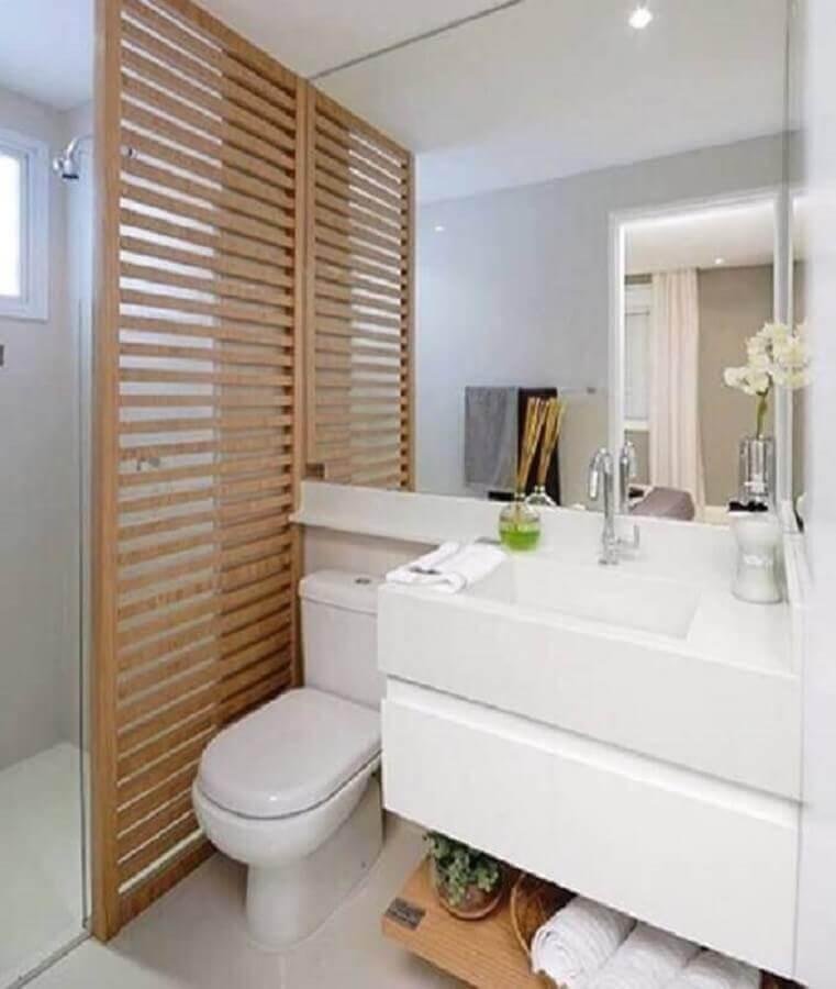 banheiro de apartamento planejado decorado com divisória de madeira Foto D+ Arquitetura