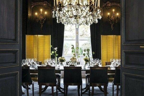 A parede preta do ambiente se harmoniza com a cor dourada dos objetos