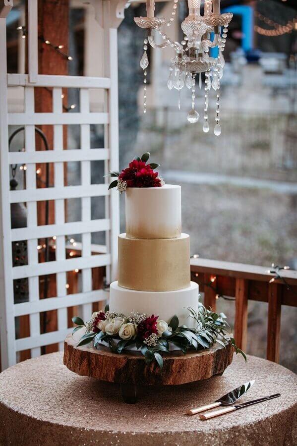 bolo de aniversário de casamento branco e dourado decorado com flores brancas e vinho Foto Assetproject