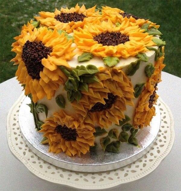 Diversas flores foram espalhadas pelo bolo para festa tema girassol