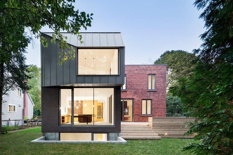 casa em l com paredes de vidro e parede de tijolinho Foto Nature Humaine