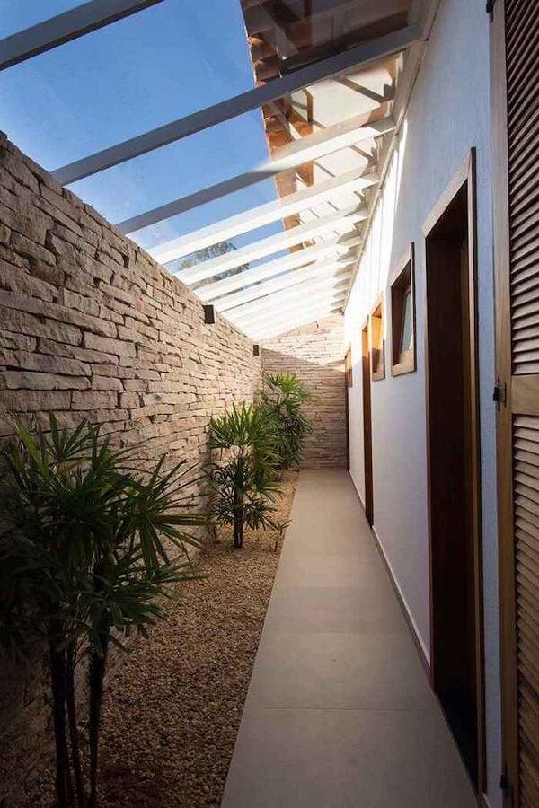 Corredor com parede de pedra e teto de vidro permite que a luz se direcione as plantas