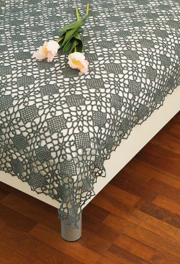 Colcha cinza e fina feita de crochê