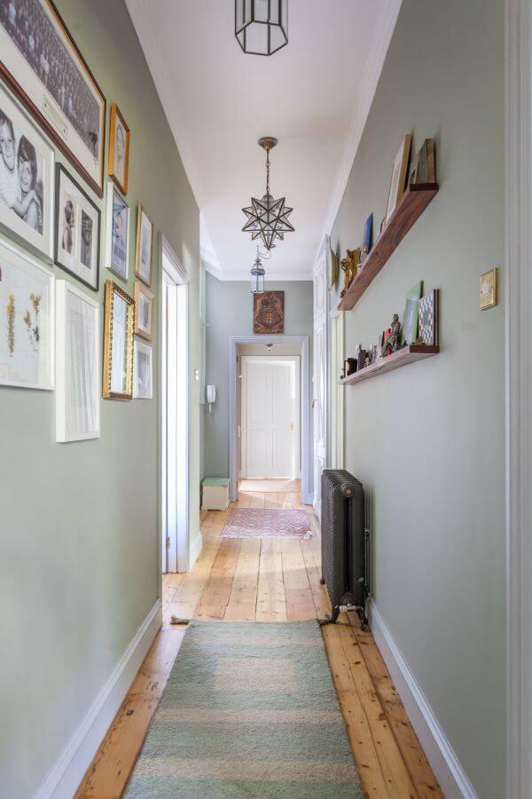 Corredor decorado com quadros e rodapé branco
