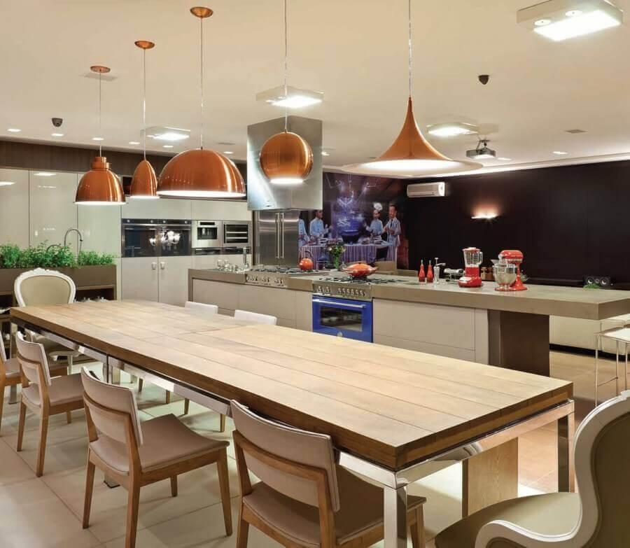 cozinha com sala de jantar integrada decorada com modelos diferentes de luminária pendente cobre Foto Anual Design