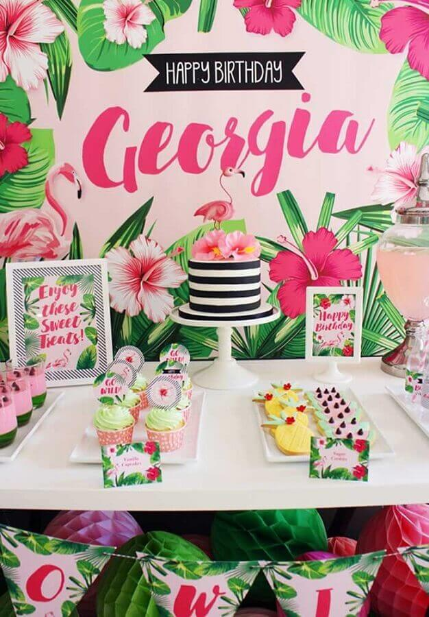 decoração de festa flamingo com painel de folhagens e bolo listrado com flores no topo Foto A Minha Festinha