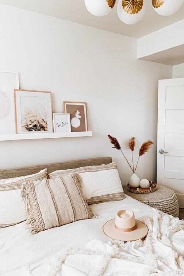 decoração em tons neutros para quarto de casal com quadros apoiados em prateleira Foto Article