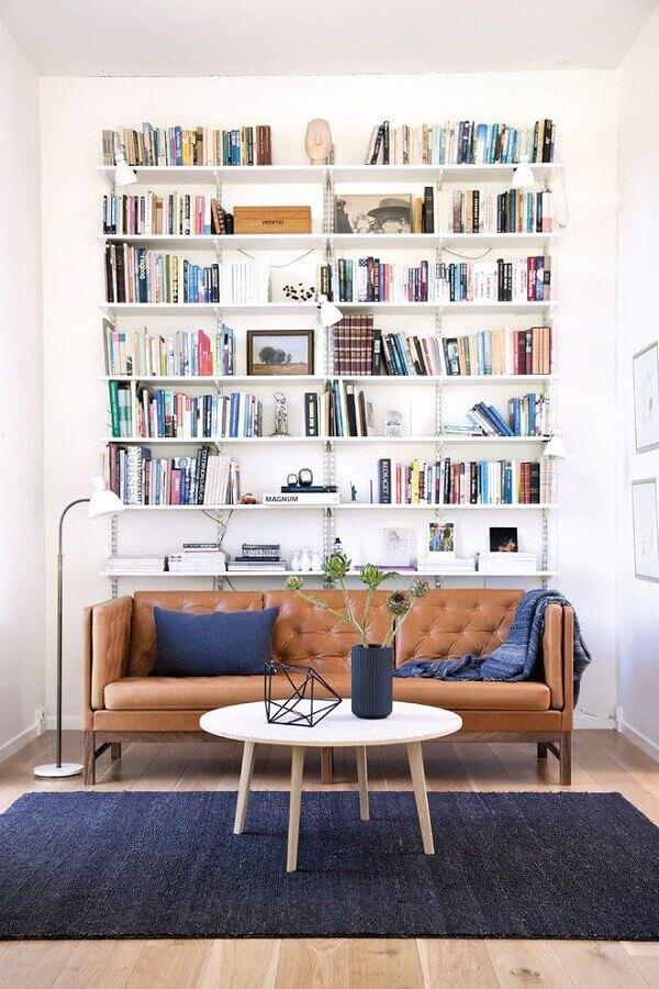 decoração simples para sala com estante de livros e sofá marrom Foto Architonic