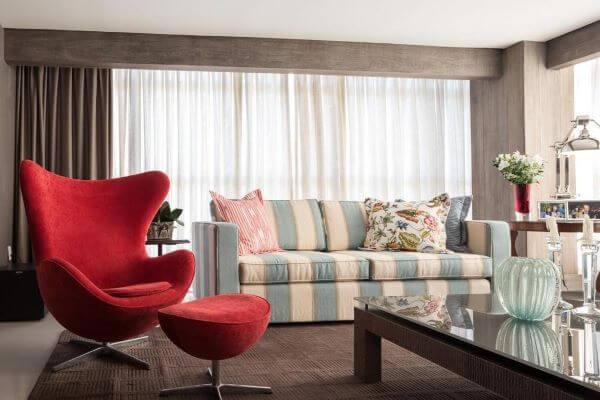 Decoração neutros com poltrona vermelha e sofá listrado