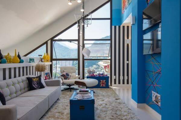 Sala de estar com parede azul e iluminada