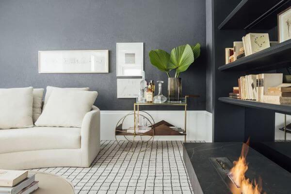 Sala de estar com parede cinza e rodape branco