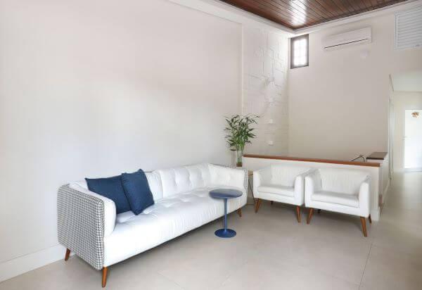 Sala de estar com poltronas brancas, clean
