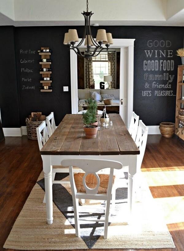 Sala de jantar com parede preta de giz e mesa de madeira