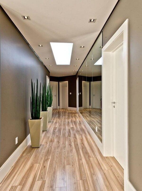 Parede espelhada e piso laminado para o corredor dessa residência