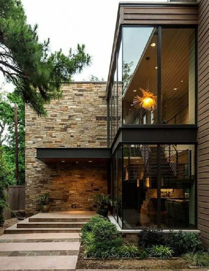 fachada casa em l moderna com paredes de vidro e revestimento de pedra Foto Pinterest