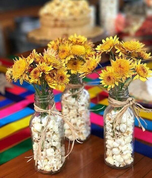 Garrafas de vidro transparente e pipoca decoram a mesa dos convidados da festa tema girassol