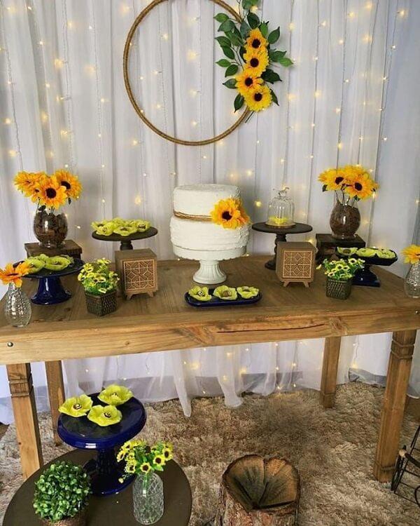 Decoração simples para festa tema girassol com cortina de pisca pisca e mesa de madeira