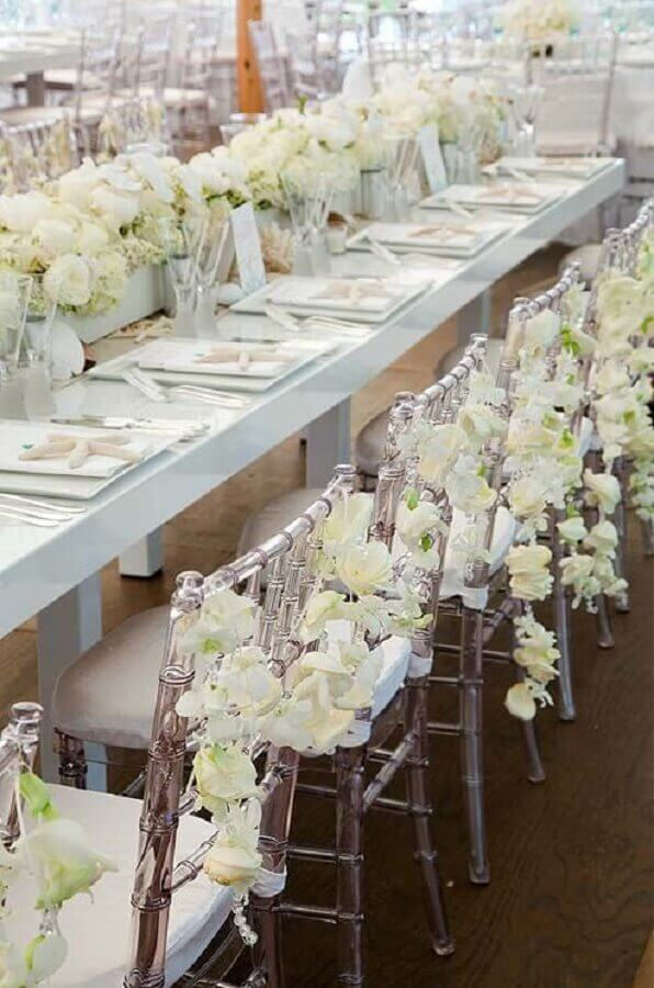 festa de aniversário de casamento decorada com arranjo de flores brancas e cadeiras de acrílico Foto Weddbook