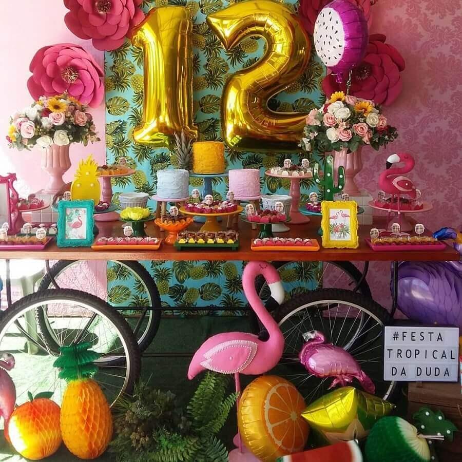 festa flamingo tropical decorada com pratos de doces coloridos e arranjo de rosas Foto Luart's Festas