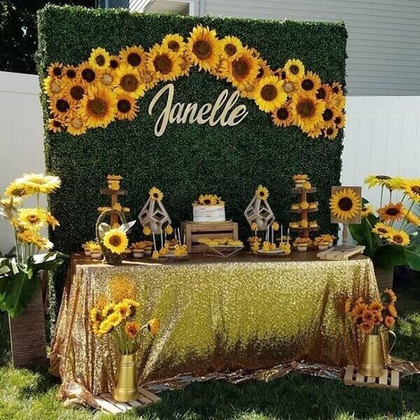 Festa de 15 anos tema girassol com painel feito com folhagens