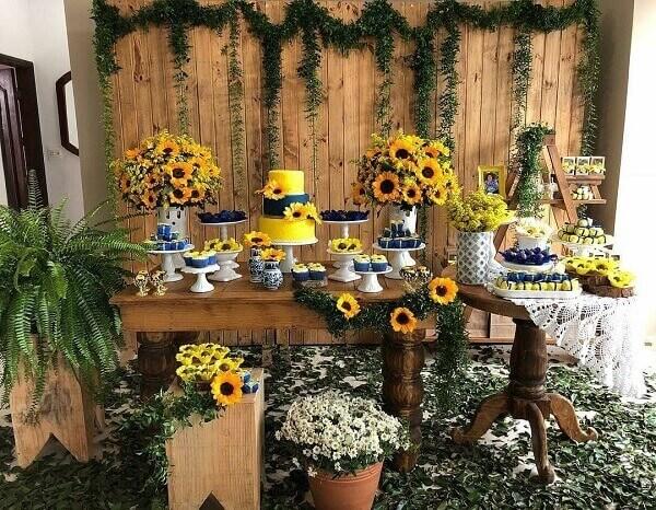 Decoração rústica para festa tema girassol com arranjos florais e painel de madeira