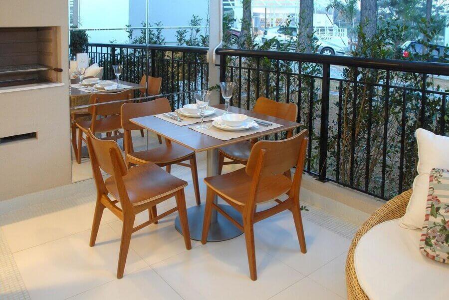 jogo de mesa e cadeira para varanda moderna com churrasqueira e parede espelhada Foto Teresinha Nigri