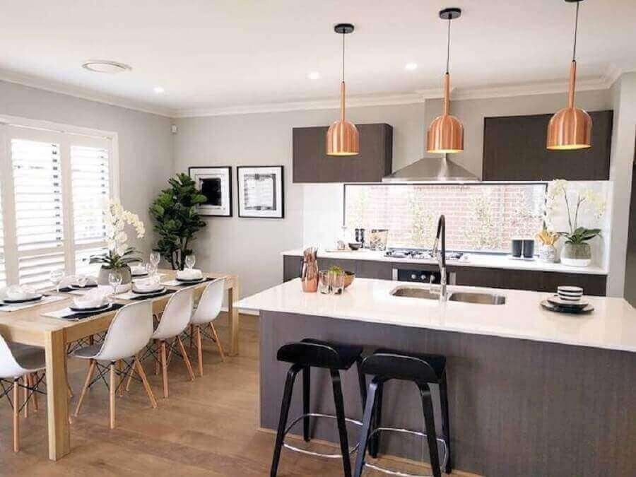 luminária pendente cobre para decoração de cozinha com ilha e mesa de madeira Foto The Style Société