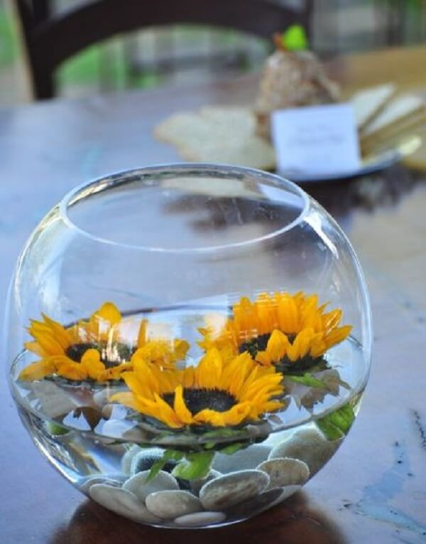 Utilize o vaso transparente com pedras, água e flores de girassol para decorar a mesa