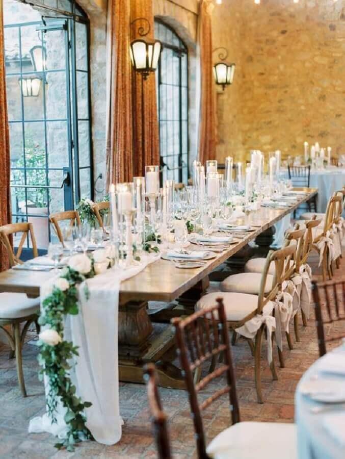 mesa decorada com folhagens rosas brancas e velas para aniversário de casamento Foto Glamour & Woods