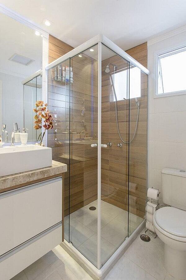 modelo de banheiro de apartamento decorado com porcelanato que imita madeira na área do box Foto LO Interiores