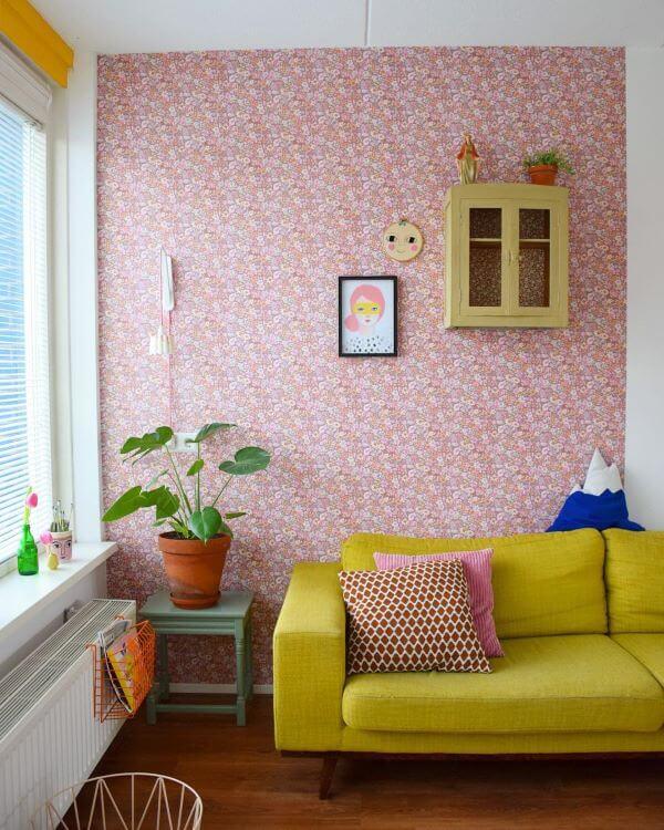 Sofá retrô amarelo com papel de parede cor de rosa