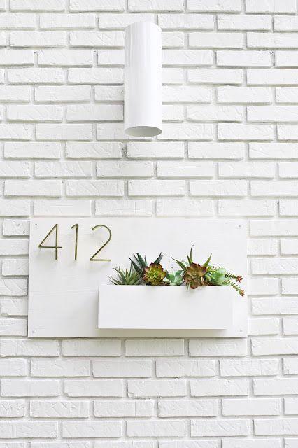 Número de casa branco com plantas